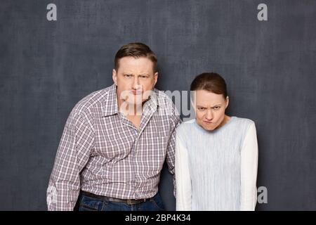 Studio waist-up portrait of funny caucasian young adult couple grimacing and making stupid angry faces, looking with dissatisfied expression from unde - Stock Photo