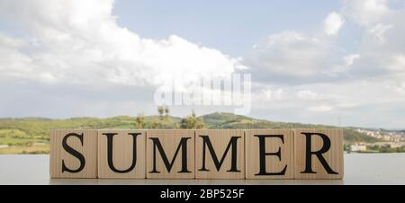 Summer text on wooden blocks. A photo was taken on the table. There are sky and mountains in the background. - Stock Photo