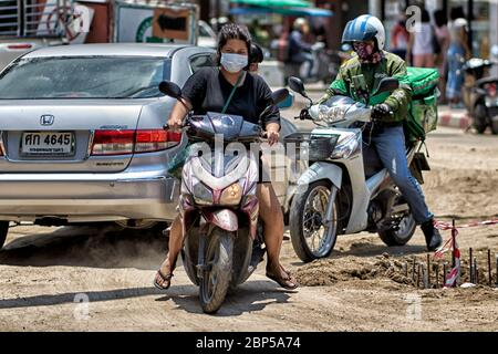 Woman riding a motorcycle and navigating treacherous road conditions through road works in Thailand Southeast - Stock Photo