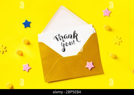 Thank you card in a golden envelope, shot from the top on a yellow background with glitter stars - Stock Photo
