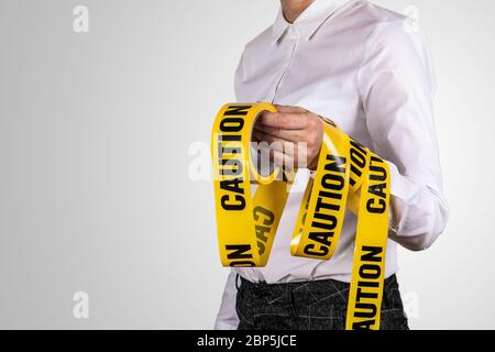 Caution tape. Security measures, restrictions, warning and keep calm concept. Woman on a gray background - Stock Photo
