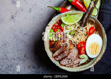 Asian spicy ramen noodles with pork, egg and vegetables in a blue bowl, gray background. - Stock Photo