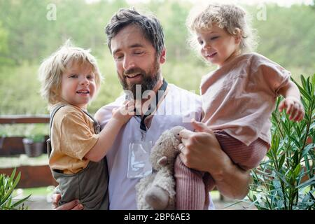 Father doctor finally at home meeting his children, end of coronavirus. - Stock Photo