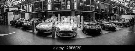 BERLIN - MAY 11, 2019: Panoramic view of the garage of Classic Remise Berlin, and repair and service offices - venue of 32th Berlin-Brandenburg Oldtimer Day. Various modern sports cars stand in a row. Black and white. - Stock Photo