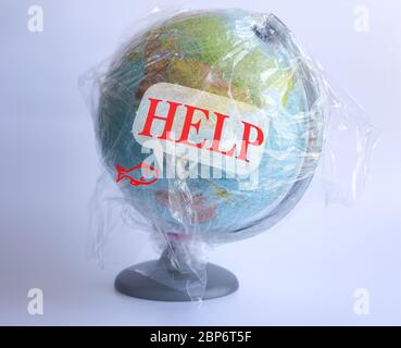 Text Help on speech bubble and icon of fish and Model planet Earth in polyethylene plastic disposable package on blue background. Ecology problems Concept pollution of environment with polyethylene plastic waste World Earth Day - Stock Photo