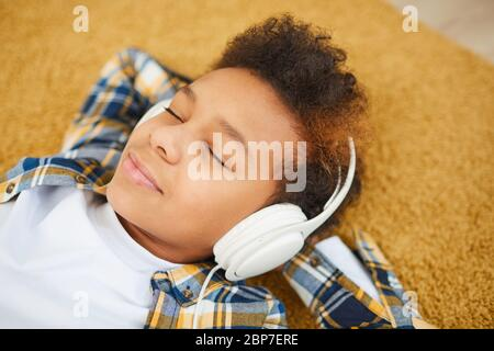 Portrait of teenage African boy wearing headphones and lying on floor while enjoying music with eyes closed, copy space
