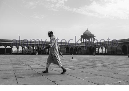 New Delhi, Delhi/ India- May 17 2020: Man in muslim dress walking across the empty Jama Masjid during Ramdan in India, Corona virus epidemic suffered - Stock Photo
