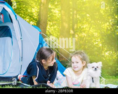 Camp in tent with children - girls sisters with little dog chihuahua sitting together near tent. Travelers sit in summer forest. Traveling with kids. Camping outdoors tourism and vacation concept. - Stock Photo