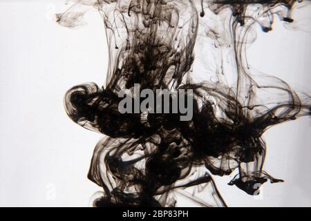 a beautiful image of a black liquid mixing in water, abstract pattern - Stock Photo