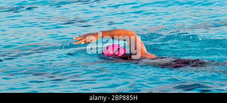 Horizontal view of a female swimmer swimming with a freestyle stroke in an outdoor pool training for a triathlon. - Stock Photo