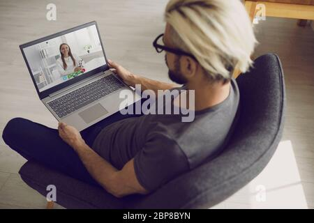 Online doctor. Male patient listens to a doctor video call using a laptop sitting in an armchair at home. - Stock Photo
