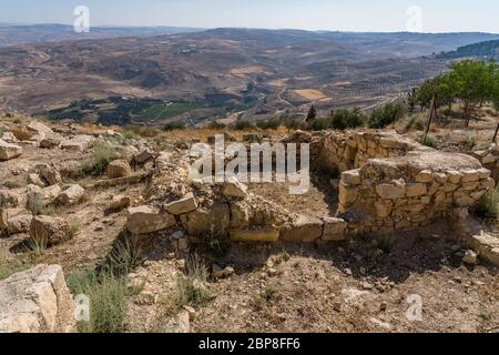 Jordan, Mount Nebo, Mount Nebo, Ruins of the Byzantine-era Siyagha monastery located by the Memorial Church of Moses. Behind is Wadi 'Uyun Musa and Moses' Spring. - Stock Photo