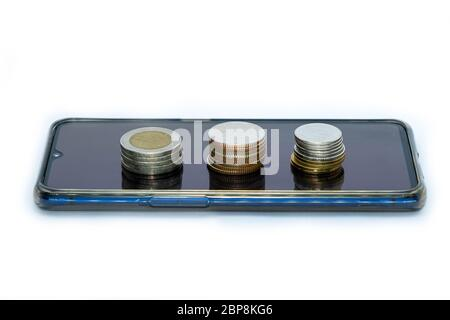 stack of coins on smart phone isolated on white background - business finance concept
