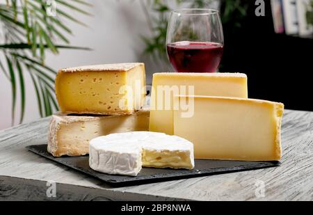 Different french cheeses with a glass of red wine - Stock Photo