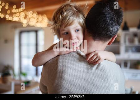 Father carrying small sick unhappy son indoors at home, comforting him. Stock Photo
