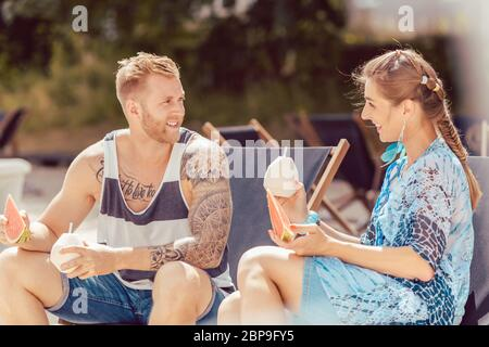 Portrait of smiling young couple sitting on chair enjoying watermelon and coconut water - Stock Photo