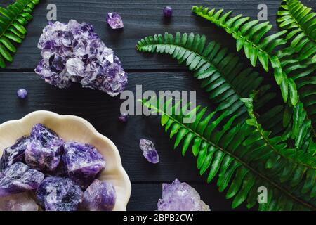Amethyst Clusters with Bowl of Rough Amethyst and Fern Leaves on Gray Background - Stock Photo