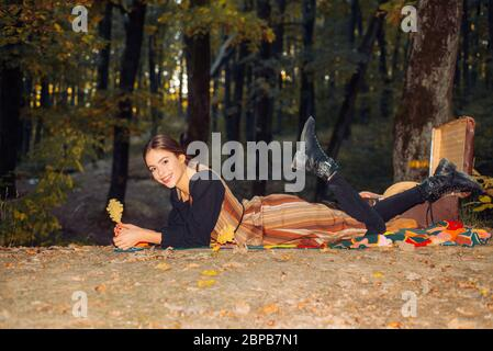 Young beautiful hipster woman in vintage grunge outfit lie on the autumnal fall orange leaves and hold oak autumn leaf. Girl resting in autumn park. F - Stock Photo