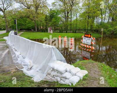 River Forest, Illinois, USA. 18th May 2020.  A temporary flood barrier constructed across Chicago Avenue holds Des Plaines River floodwater away from this western suburb of Chicago. - Stock Photo