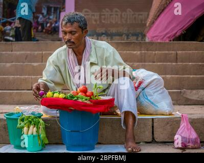 Varanasi, India - November 11, 2015. An Indian man prepares to sell fresh vegetables to pilgrims and tourists while sitting on the ghat steps. - Stock Photo