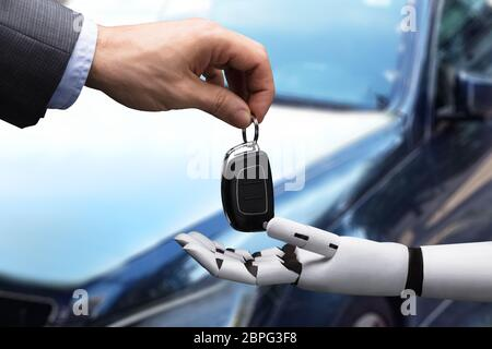 Close-up Of A Businessperson's Hand Giving Car Key To Robot Stock Photo