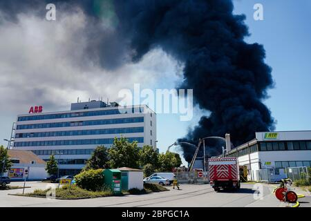 Ladenburg, Germany. 19th May, 2020. Clouds of smoke are rising from a plastics factory next to a building belonging to the ABB company. Due to a major fire in a factory building in Ladenburg (Rhine-Neckar district) a large cloud of smoke formed over the region. Credit: Uwe Anspach/dpa/Alamy Live News - Stock Photo