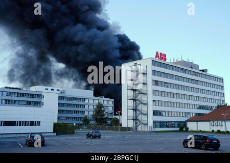 Ladenburg, Germany. 19th May, 2020. Clouds of smoke rise from a plastics factory behind a building belonging to the ABB company. Due to a major fire in a factory building in Ladenburg (Rhine-Neckar district) a large cloud of smoke formed over the region. Credit: Uwe Anspach/dpa/Alamy Live News - Stock Photo