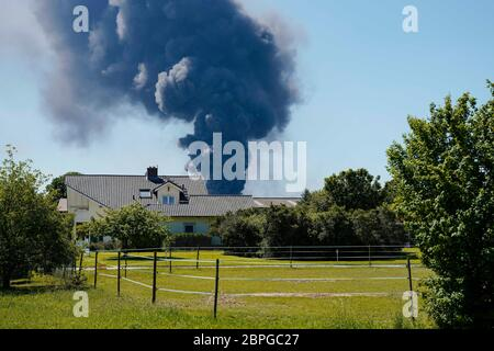 Ladenburg, Germany. 19th May, 2020. Clouds of smoke from a fire in a plastics factory rise into the sky behind a house. Because of the large fire in a factory building in Ladenburg (Rhine-Neckar district) a large cloud of smoke formed over the region. Credit: Uwe Anspach/dpa/Alamy Live News - Stock Photo