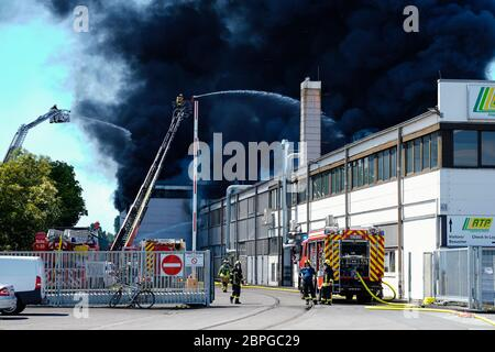 Ladenburg, Germany. 19th May, 2020. Firefighters on turntable ladders extinguish the fire in a plastics factory. Because of the large fire in a factory building in Ladenburg (Rhine-Neckar district) a large cloud of smoke formed over the region. Credit: Uwe Anspach/dpa/Alamy Live News - Stock Photo