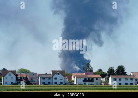 Ladenburg, Germany. 19th May, 2020. Clouds of smoke from a fire in a plastics factory rise into the sky behind houses. Because of the large fire in a factory building in Ladenburg (Rhine-Neckar district) a large cloud of smoke formed over the region. Credit: Uwe Anspach/dpa/Alamy Live News - Stock Photo