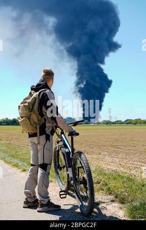 Ladenburg, Germany. 19th May, 2020. A cyclist looks at the clouds of smoke from a fire in a plastics factory. Because of the large fire in a factory building in Ladenburg (Rhine-Neckar district) a large cloud of smoke formed over the region. Credit: Uwe Anspach/dpa/Alamy Live News - Stock Photo