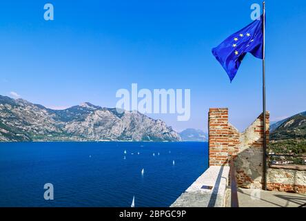 European Union flag on the background of lake Garda and Malcesine town. View from the Scaliger Castle, Italy. - Stock Photo