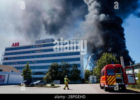 Ladenburg, Germany. 19th May, 2020. Clouds of smoke rise from a plastics factory next to a building belonging to the ABB company. Due to a major fire in a factory building in Ladenburg (Rhine-Neckar district) a large cloud of smoke formed over the region. Credit: Uwe Anspach/dpa/Alamy Live News - Stock Photo