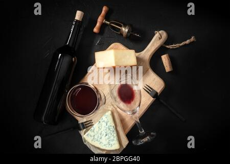 Wine and cheese tasting, shot from above on a black background, with a vintage corkscrew and a bottle - Stock Photo