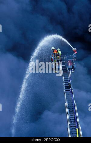 Ladenburg, Germany. 19th May, 2020. A fireman on a turntable ladder extinguishes the fire in a plastics factory by means of clouds of smoke. Because of the large fire in a factory building in Ladenburg (Rhine-Neckar district) a large cloud of smoke formed over the region. Credit: Uwe Anspach/dpa/Alamy Live News - Stock Photo