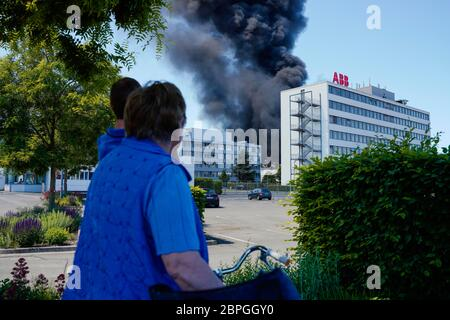 Ladenburg, Germany. 19th May, 2020. People look at clouds of smoke rising from a plastic factory. Because of the large fire in a factory building in Ladenburg (Rhine-Neckar district) a large cloud of smoke formed over the region. Credit: Uwe Anspach/dpa/Alamy Live News - Stock Photo