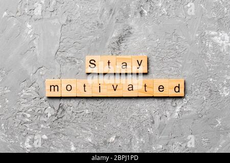 Stay motivated word written on wood block. Stay motivated text on cement table for your desing, concept. - Stock Photo