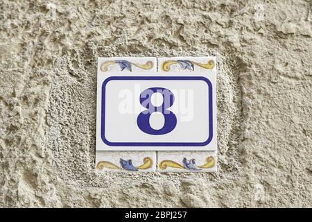 Number eight on a wall, detail of a number of information on a wall of a house, even number