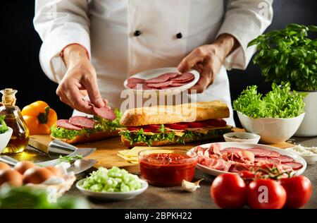Chef preparing a crusty baguette sandwich with cold sliced salami and fresh salad trimmings in a close up on his hands - Stock Photo