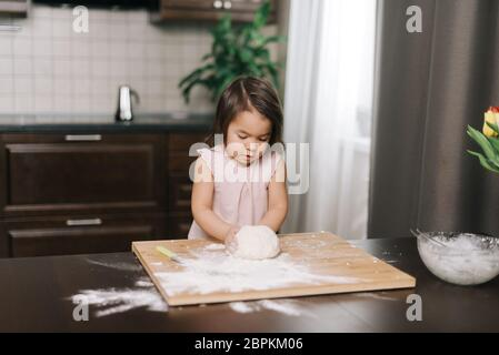 Cute beautiful little girl prepares dough for baking cookies at the table - Stock Photo