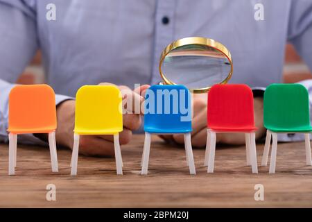 Close-up Of A Businessperson's Hand Looking At Vacant Colorful Chairs Through Magnifying Glass - Stock Photo