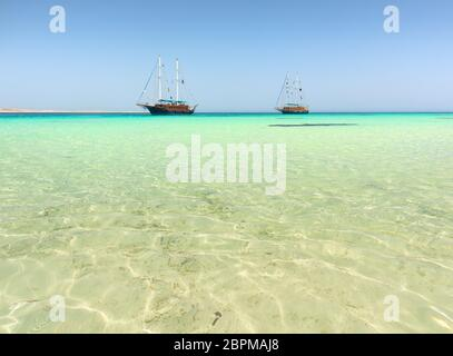 Two sailboats in turquoise sea under sunlight - Stock Photo