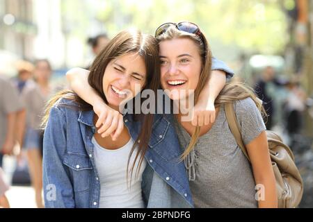 Two funny friends laughing loud walking in the street - Stock Photo