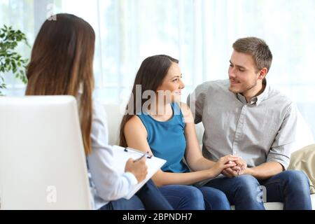 Happy couple listening to a marriage counselor and looking each other during therapy at home - Stock Photo