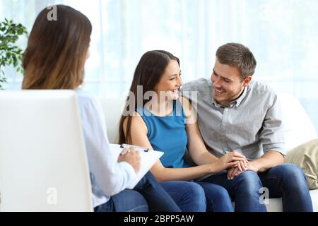 Happy marriage after couple therapy sitting on a couch at home or consultation - Stock Photo