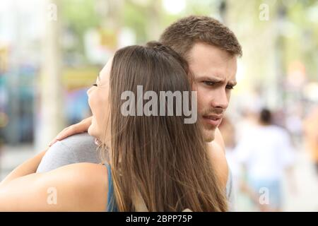 Discontent boyfriend hugging his partner on the street - Stock Photo