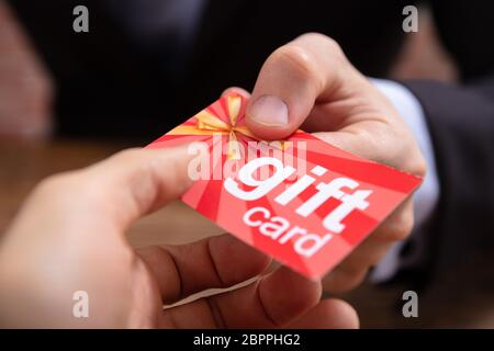 Close-up Of Businessperson's Hand Giving Red Gift Card To Other Businessperson Stock Photo