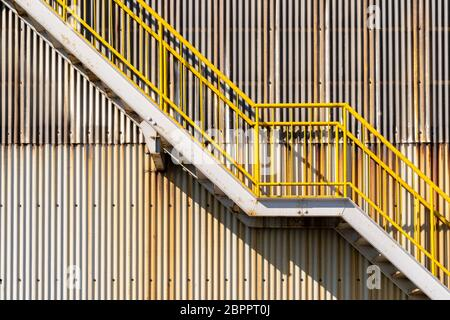exterior of metal sheet warehouse wall and fire exit stair - Stock Photo