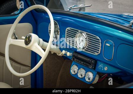 TORONTO, CANADA - 08 18 2018: Interior with steering wheel with logo, speedometer, revs dial on front panel of blue 1955 Volkswagen Beetle oldtimer - Stock Photo