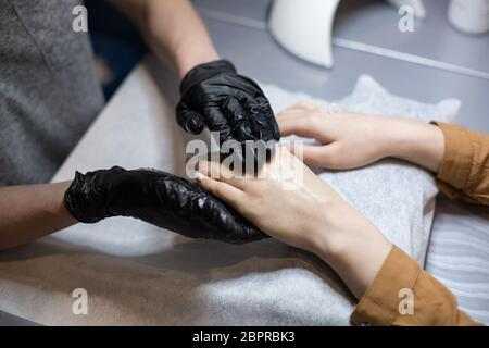 Close-up of a manicurist doing moisturizing and hand massage for a client. The theme is skin care and body beauty. Spa and Manicure concept. Soft skin